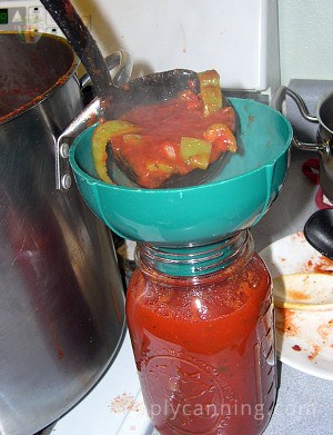 Spooning spaghetti sauce into a canning jar.