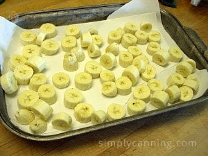 Slices of bananas layered over a freezer paper lined cookie sheet.