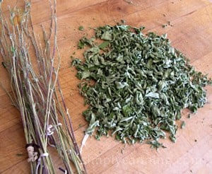 A pile of dried herb leaves sitting next to a pile of bare herb stems.