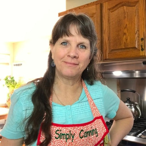 Sharon in her kitchen wearing a red Simply Canning apron.