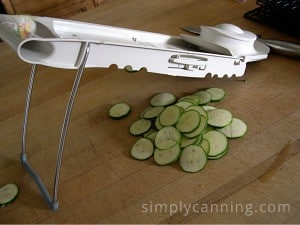 Slicing a zucchini into thin slices using the Mandolin slicer.
