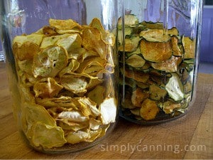 Jars filled with dried yellow and green zucchini chips.