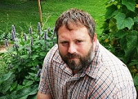 Brad sitting in his vegetable garden with plants visible behind him.