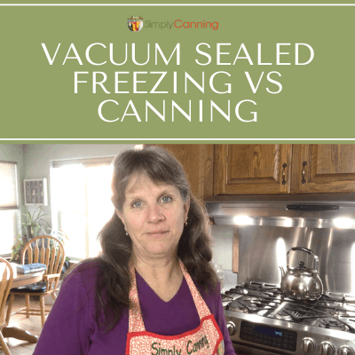 Sharon wearing a Simply Canning apron and standing next to her stovetop with the kitchen table in the background.