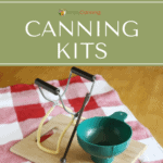 Canning funnel and jar lifter and lid lifter sitting on a wooden cutting board.