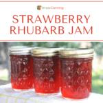 Three bright red jars of strawberry rhubarb jam.