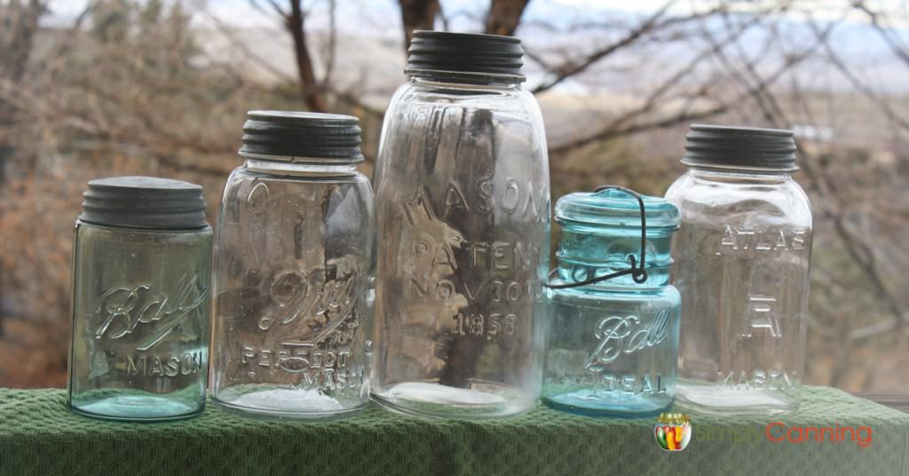 Blue and clear glass antique canning jars sitting outdoors.