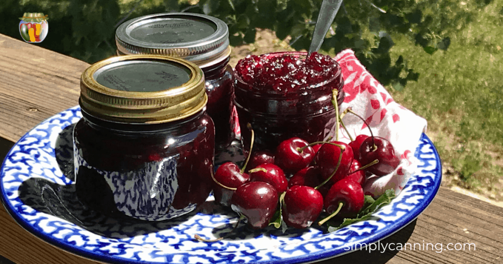 Rich red cherry jam in jars sitting a plate with cherries on the side.