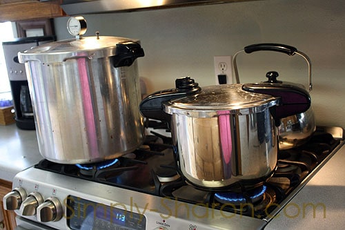 Presto pressure canner sitting next to a smaller pressure cooker on the stove.