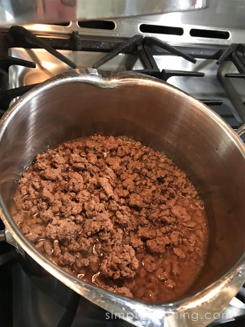 Ground meat cooking in a pan.