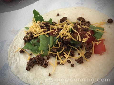 Seasoned taco meat with lettuce and cheese and tomato on a flour tortilla.
