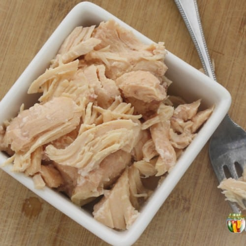 Shredded cooked chicken in a square dish with a fork sitting beside it.
