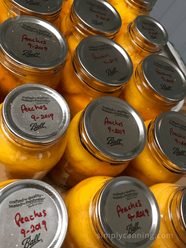 Jars of peaches labeled accordingly on the flat lids.