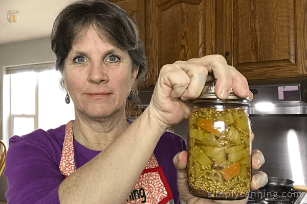 Tightening the screw band on a canning jar.