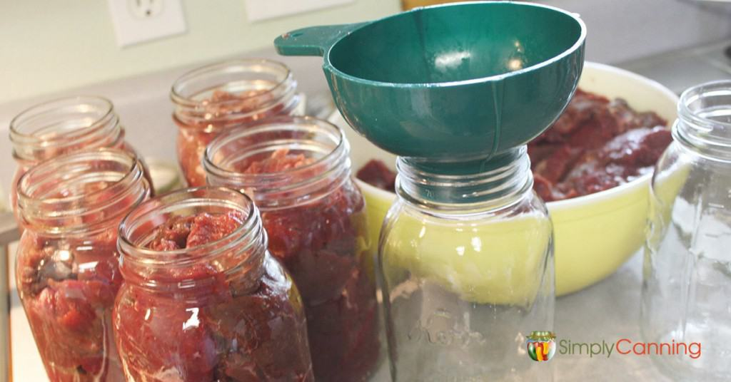 Packing meat into jars for canning meat page.