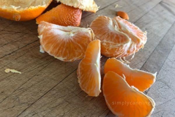 Bright orange segments sitting on a cutting board.