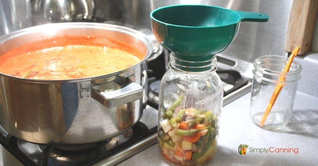 Canning jar filled with solid soup ingredients with a boiling pot of soup to the side.