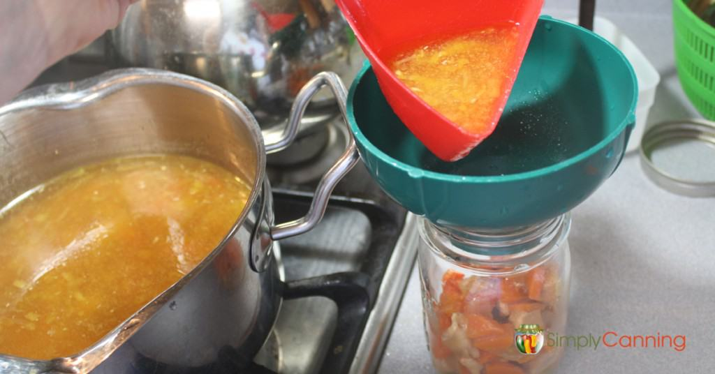 Pouring chicken soup into jars for canning.