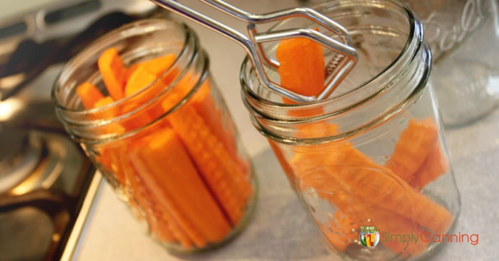 Using tongs to put carrot sticks into clean canning jars.