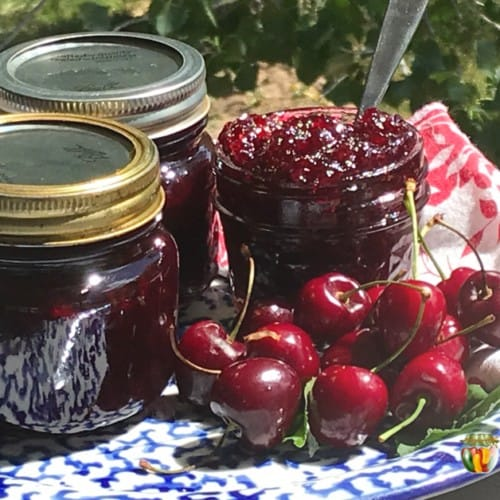 An open jar of cherry jam with more jars of jam and fresh cherries beside it.