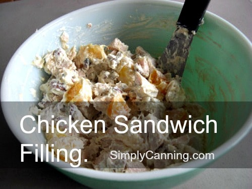 Chicken salad sandwich filling mixed up in a lime green bowl.