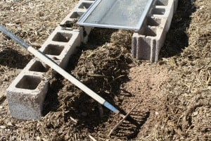 Raking up a layer of straw during the cold frame construction.