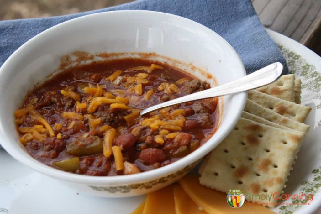 A bowl of chili topped with shredded cheese and served with crackers on the side.