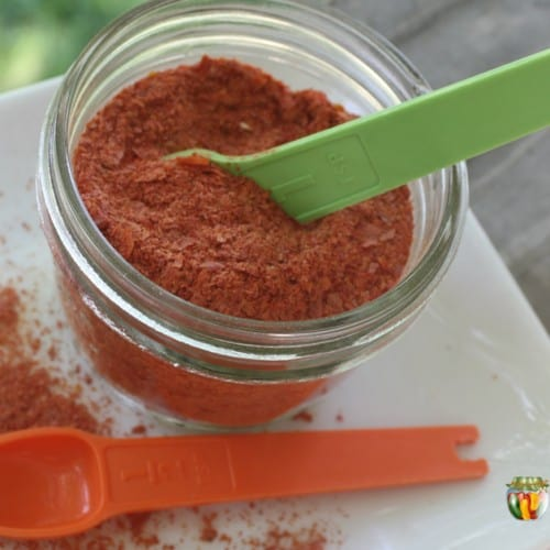 A jar filled with dried tomato powder with measuring spoons in and around the jar.
