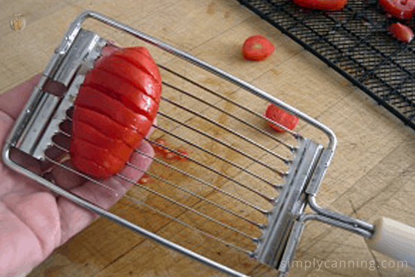 Slicing a long tomato using the vintage tomato slicing tool.
