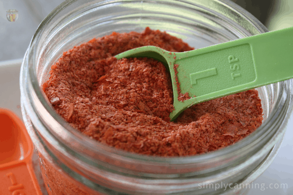 Scooping a spoonful of dried tomato powder from a full jar.