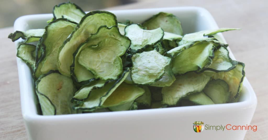 Slices of dehydrated green zucchini in a white serving dish.