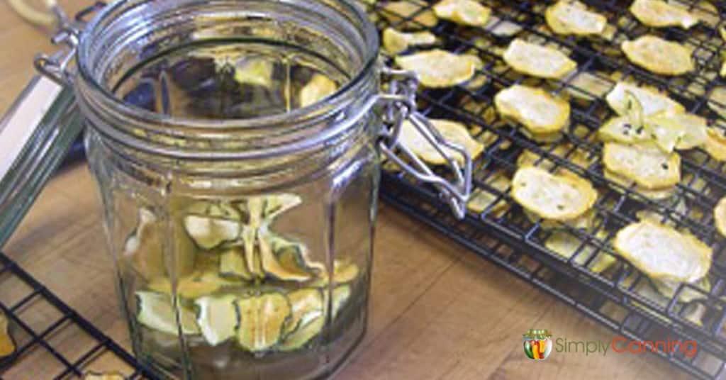Putting dehydrated zucchini into a snap close jar.