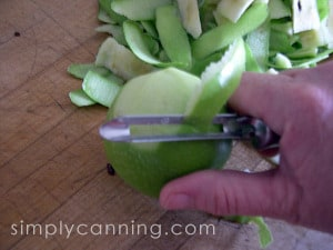 Using a vegetable peeler to peel green skin from an apple.