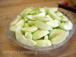 A pie plate filled with peeled and sliced apples.