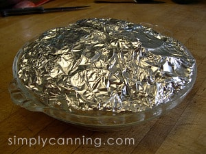Apple slices wrapped in foil inside a glass pie plate.