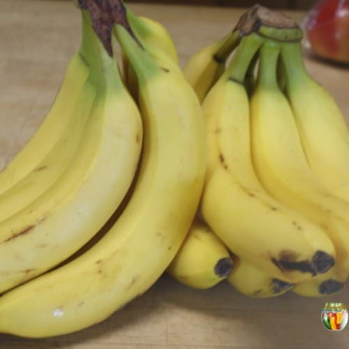 Two bunches of bright yellow bananas with bags of apples in the background.