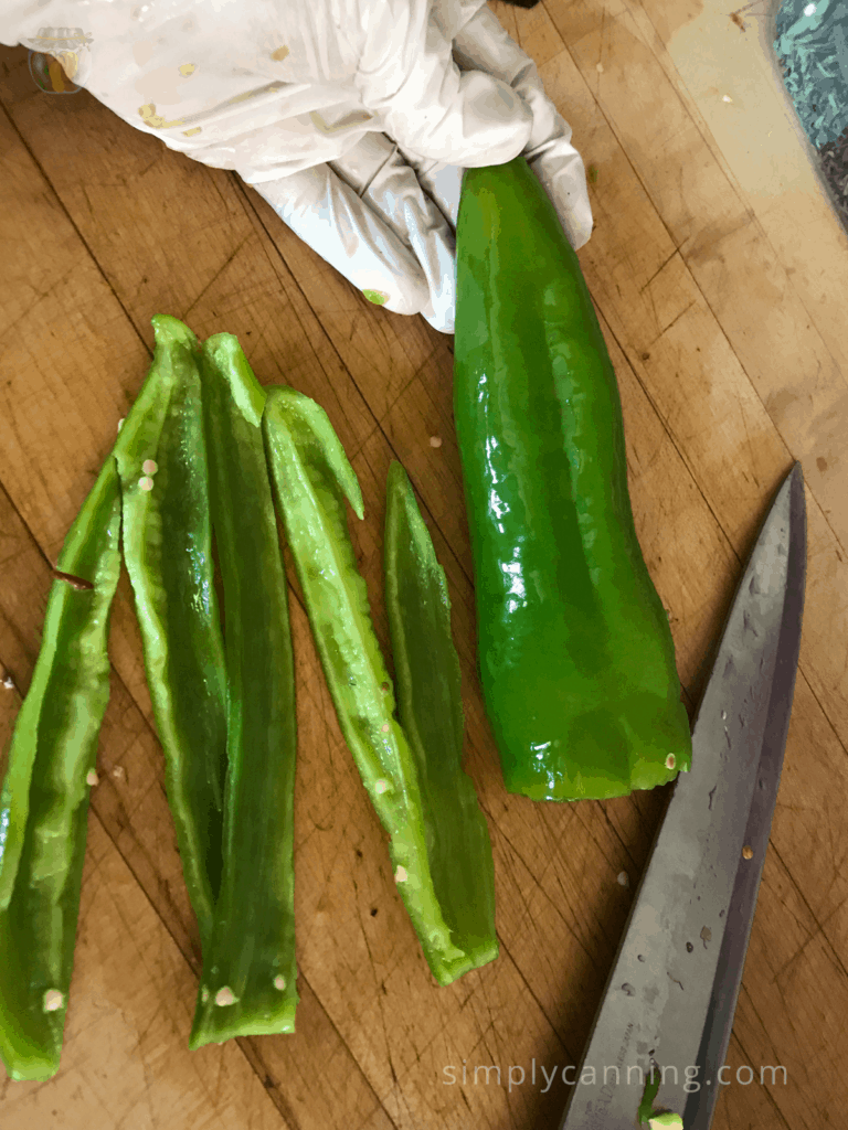 Slicing long green peppers into pieces using a sharp knife.