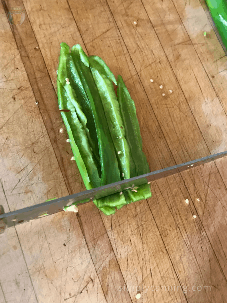 Chopping sliced green peppers into smaller pieces using a sharp knife on a wooden cutting surface.