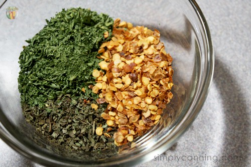 Dried herbs and spices in a glass dish.