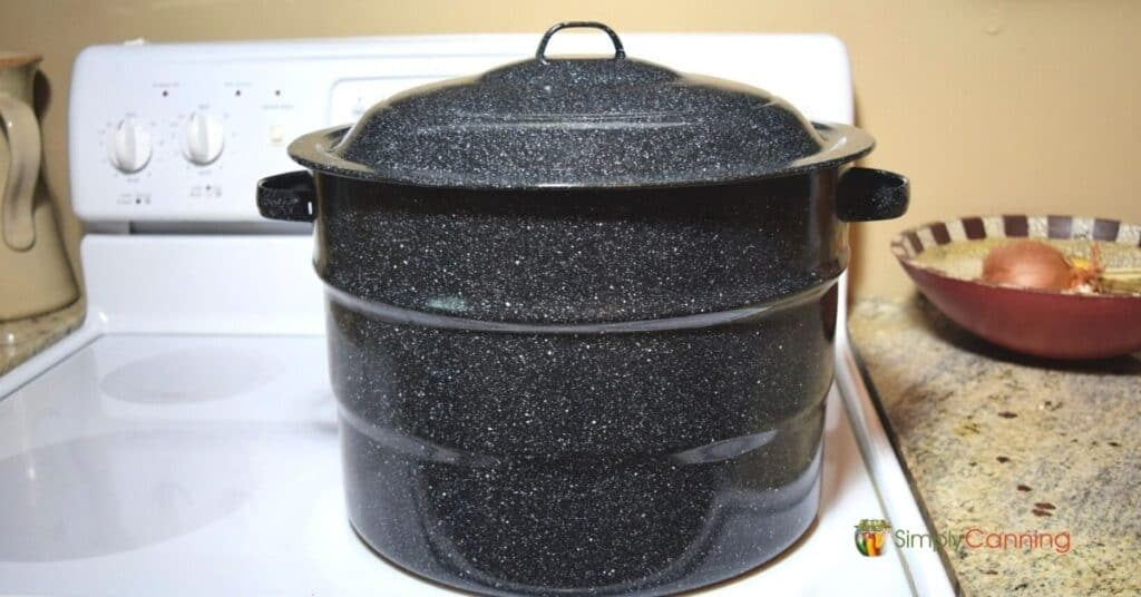 A graniteware canner sitting on a white glasstop stove.