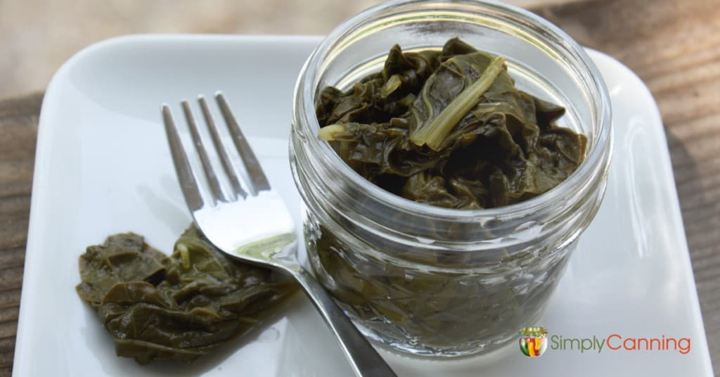 A small jar filled with cooked greens and a fork to the side.