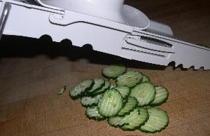 Using mandolin to crinkle cut cucumbers into slices.