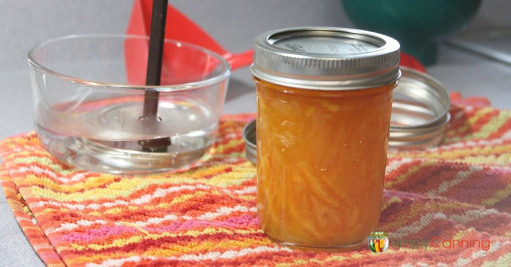 A jar of orange marmalade with various canning supplies around it.