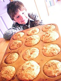 My son looking over a muffin tin filled with freshly baked orange muffins.