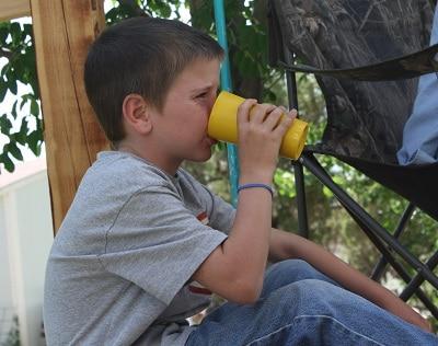 My son enjoying a cold peach slushy outdoors while sitting in the shade.