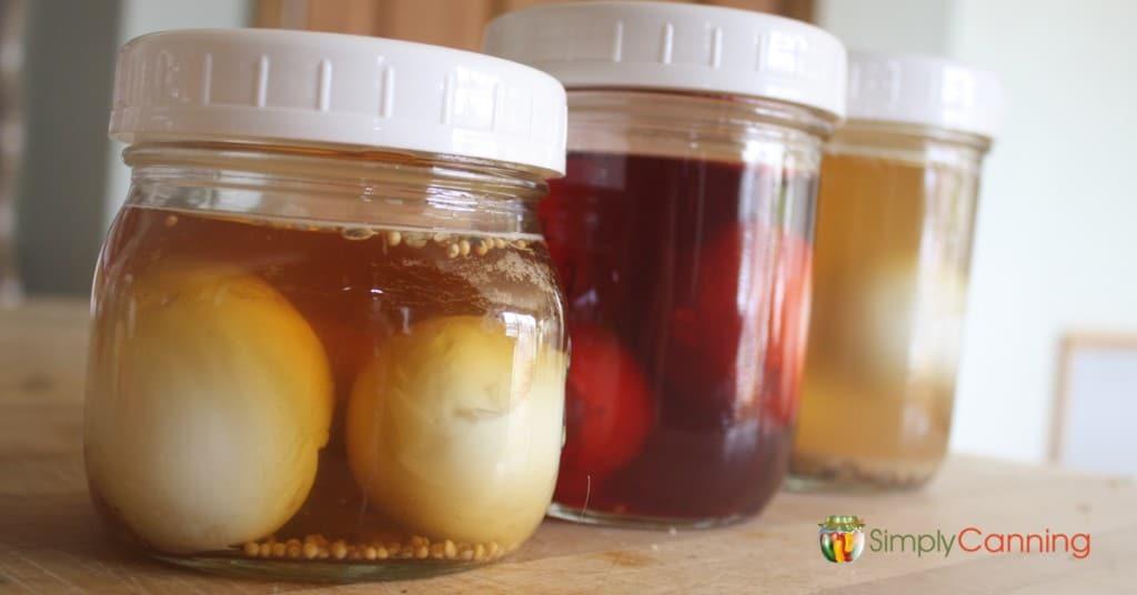Jars of pickled eggs in various colors of brine.