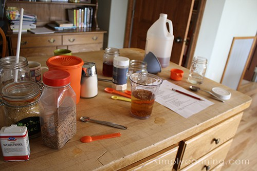 Vinegar and other pickling ingredients and supplies scattered over the butcher block countertop.