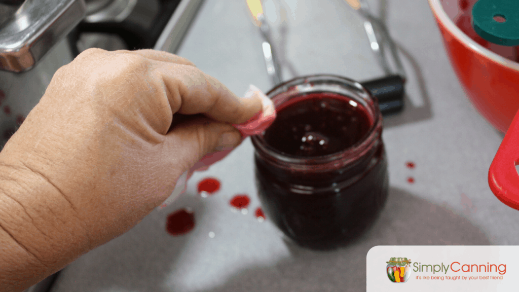 Wiping the rim of a jar of plum jam with a wet paper towel.