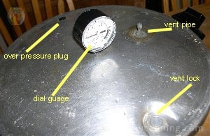 Dial gauge lid with the dial in the middle and the vent pipe off to the side.