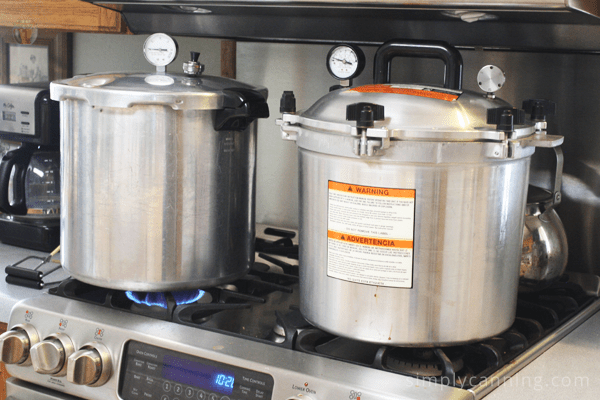 Presto pressure canner next to an All American pressure canner on the stovetop.